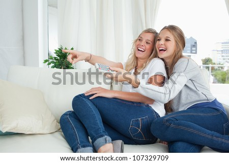 A smiling couple of girls on the couch as they watch tv