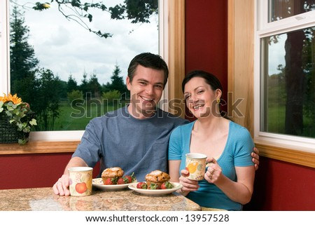 A smiling couple sitting by large windows having breakfast.  The man has his arm around the woman who is holding a coffee cup. - stock photo