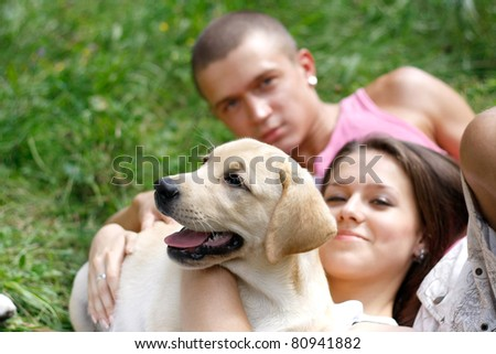 A smiling couple with their dog outdoors - stock photo