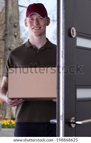 A smiling courier standing at the door with a package