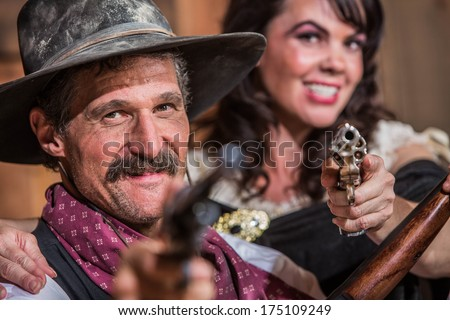 A Smiling Cowboy and Saloon Girl Point Their Weapons at You - stock photo