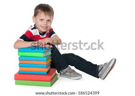 A smiling cute boy is sitting on the floor near the pile of books against the white background