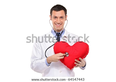 A smiling doctor examining a red heart shaped pillow with a stethoscope against white background - stock photo