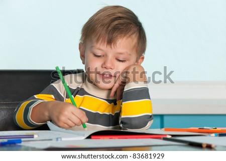 A smiling drawing little boy is sitting at the desk - stock photo