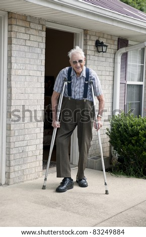 A smiling elderly man with crutches standing outside of his apartment - stock photo