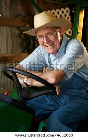 A smiling farmer sitting on his tractor in the barn.