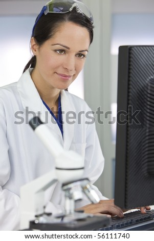 A smiling female medical or scientific researcher or woman doctor using a computer in a laboratory with microscope and other equipment in the foreground.