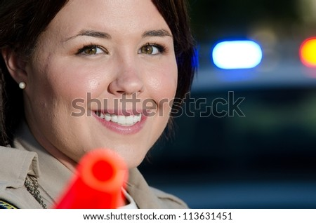 a smiling female police officer holds her flashlight with its orange cone as she's about to direct traffic.