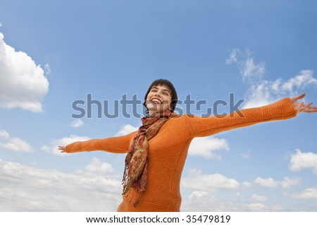 A smiling female posing with outstretched arms.  Clouds are in view behind her.  Horizontally framed shot.