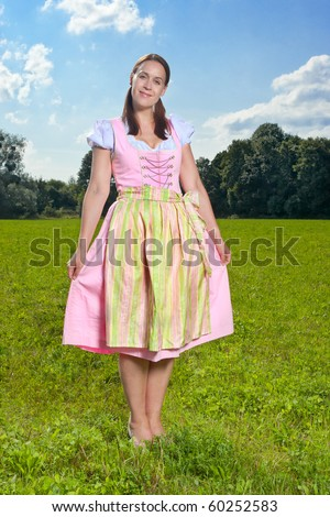 A smiling German girl in a traditional Dirndl dress in a sunny meadow. - stock photo
