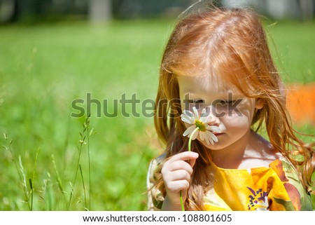 A smiling ginger-haired girl with a flower in the field - stock photo