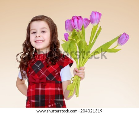 A smiling girl in a red dress with a bouquet of pink tulips.Happiness concept,happy childhood