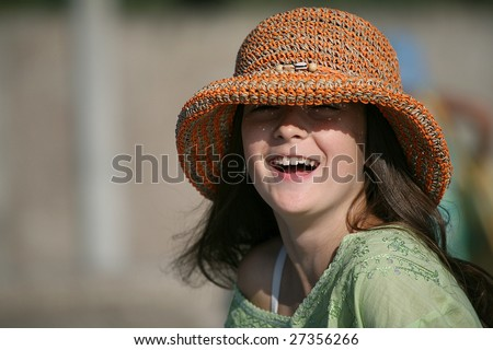 a smiling girl in hat a pleased smile upon one's face - stock photo