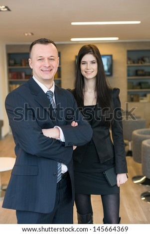 A smiling girl with a man in business suits standing in the room