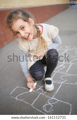 A smiling girl with a pigtail ends draw hopscotch on the pavement - stock photo