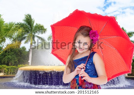 A smiling girl with a red umbrella in the resort.spring season,fun outdoors,happy childhood,sweet child having fun outdoor,smiling toddler portrait - stock photo