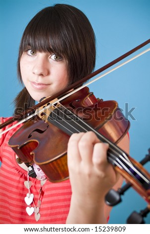 A smiling girl with big hazel eyes playing her viola. - stock photo