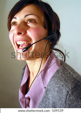 a smiling girl with headset phone at a call center.