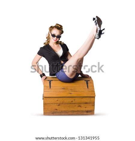 A smiling glamorous pin up woman wearing black top and blue shorts, seated with legs in the air on a pine trunk isolated on white background - stock photo