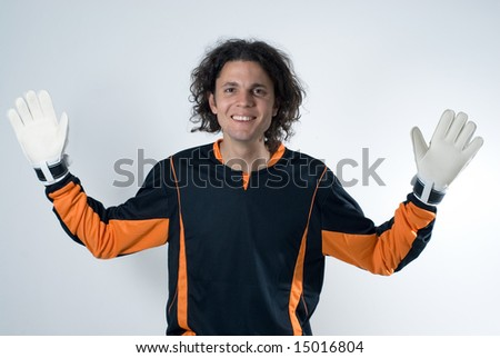 A smiling goalie with his hands stretched out defensively.  He is staring at the camera, and is wearing white gloves. Horizontally framed shot. - stock photo