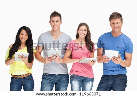 A smiling group looking at the camera and holding tablets in their hands