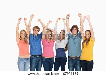A smiling group of friends looking at the camera with their hands raised up - stock photo