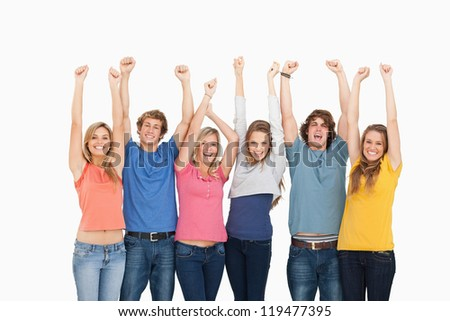A smiling group of friends with their hands in the air as they look at the camera - stock photo