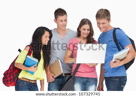 A smiling group of people looking into a laptop
