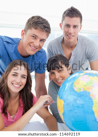 A smiling group of people sitting beside a globe as they look into the camera - stock photo