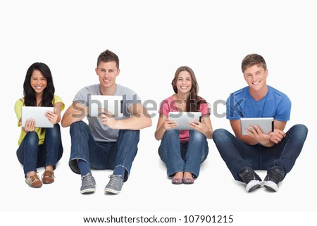 A smiling group of people sitting on the ground beside each other while using tablets and looking at the camera - stock photo