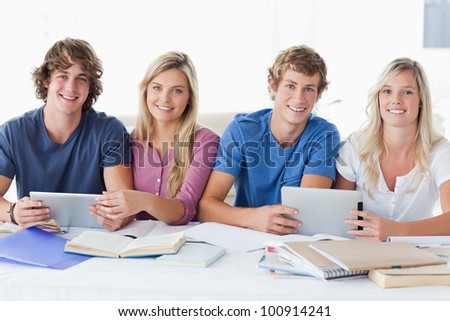 A smiling group of students look at the camera as they help one another with work