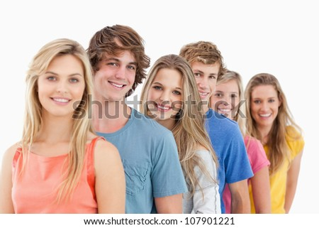A smiling group standing behind each other at an angle while looking into the camera - stock photo