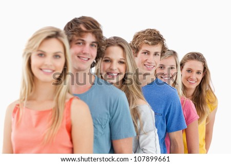 A smiling group standing behind each other while looking at the camera - stock photo