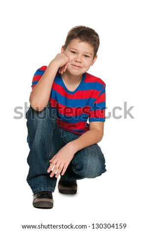 A smiling handsome boy in striped shirt sits on the floor on the white background