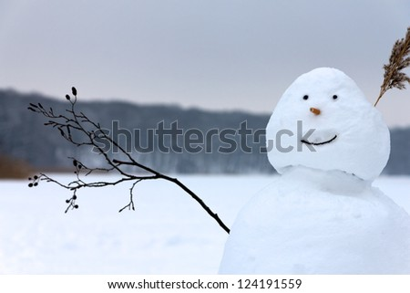 A smiling happy snowman raises the twig it has for an arm in greeting before the background of a frozen lake and forest. - stock photo