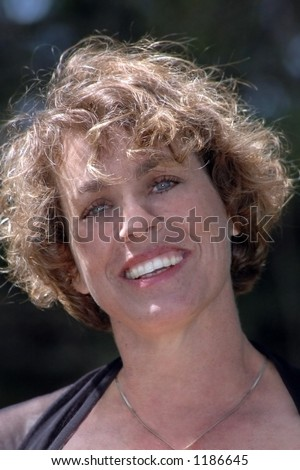 A smiling head shot of a beautiful 30 something woman.