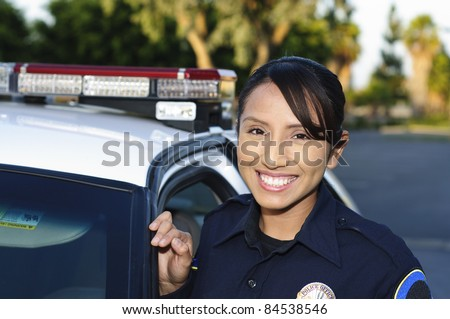 a smiling Hispanic police officer next to her patrol car. - stock photo
