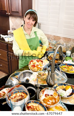 A smiling homemaker gets ready to wash a mass of filthy dishes. - stock photo