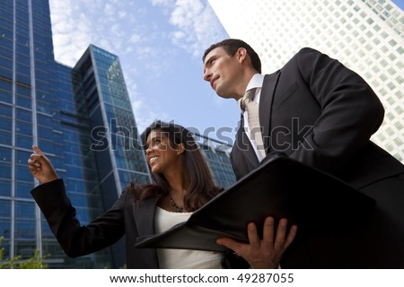 A smiling Indian Asian businesswoman and her male colleague taking part in a happy business meeting outside in a modern city environment - stock photo