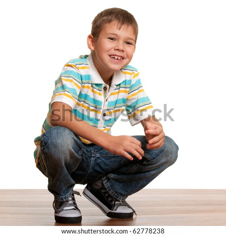 A smiling kid in casual clothes squats above the wooden background; isolated on white