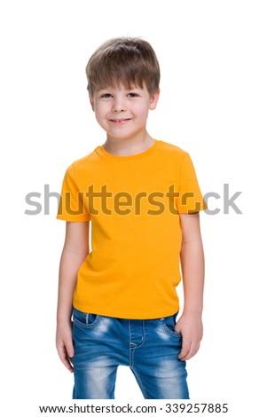 A smiling little boy in a yellow shirt stands against the white background