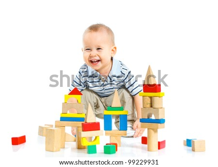A smiling little boy is building a toy block sitting on the floor - stock photo