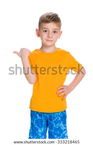 A smiling little boy shows his finger to the side against the white background