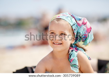 A smiling little girl child with a colorful handkerchief on his head. Hot sunny summer day at the beach. Selective focus on child's face. - stock photo