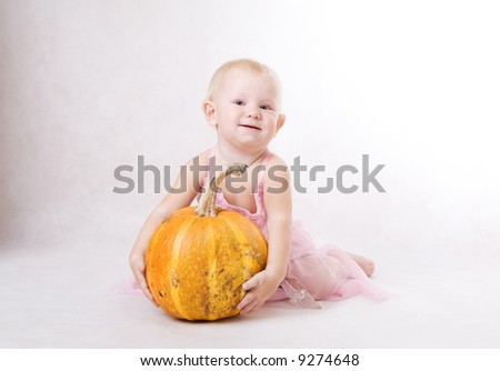a smiling little  girl embraces a pumpkin and a crystal shoe near by