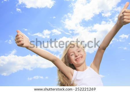 A smiling little girl in white blank t-shirt showing thumbs up over blue sky background - stock photo