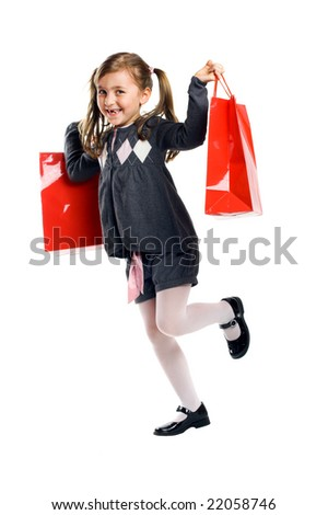 a smiling little girl isolated on white background with shopping bags - stock photo