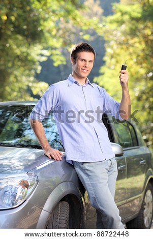 A smiling male holding a car key posing next to his automobile - stock photo