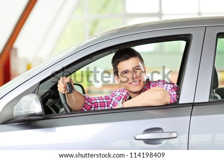 A smiling male sitting in his automobile and holding a car key - stock photo