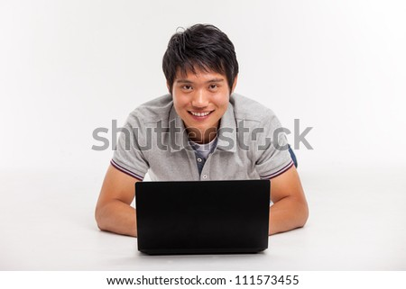 A smiling male working on a laptop isolated on white background - stock photo